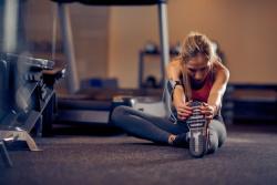 Stretching Leg on Gym Floor